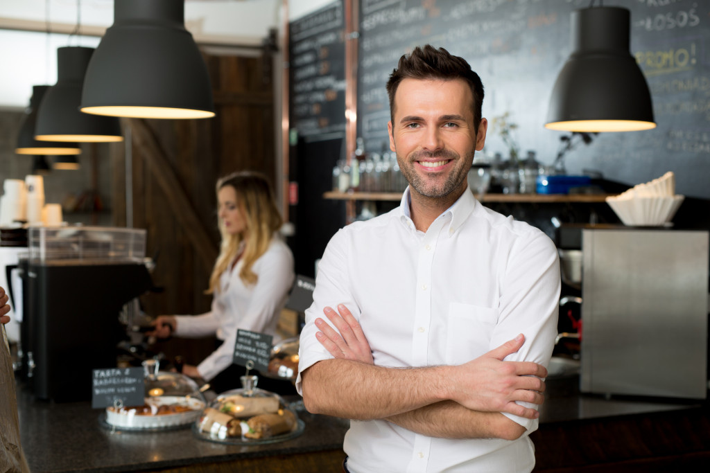 Businessowner with employee behind him making coffee